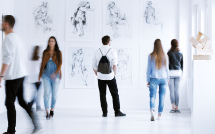 Young man with rucksack on back visiting art gallery with drawings and sculpture